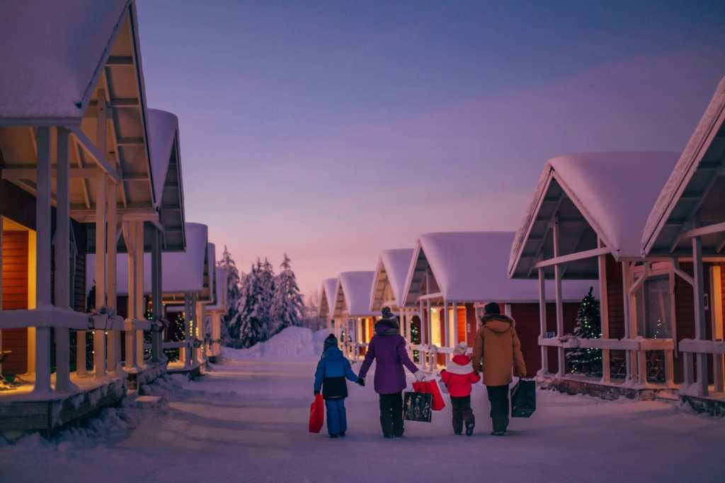picture of family holding hands as they walk through Santa Claus Holiday Village