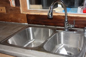 Wood Packsplash, Cement Counters, Stainless sink and faucet