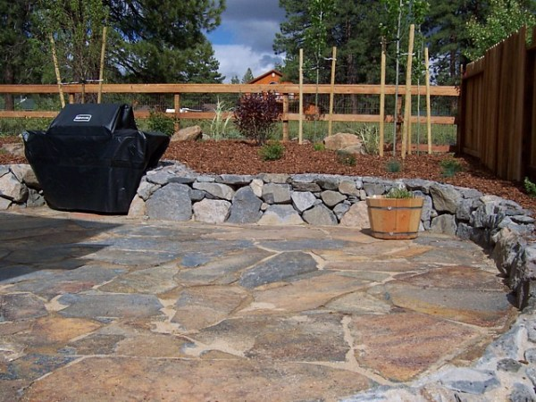 flagstone patio with rock wall