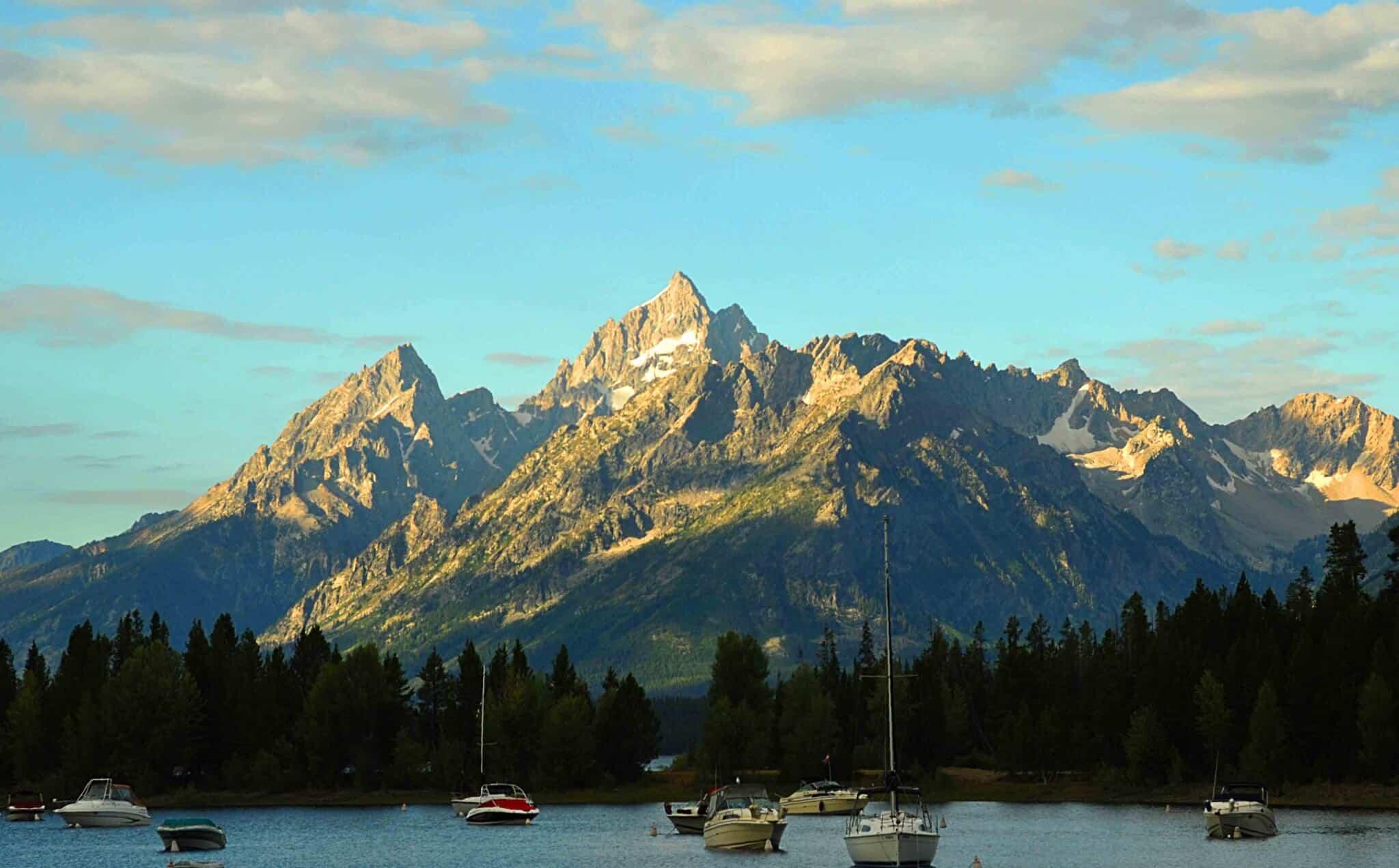 Sailboats moared beneath the Tetons at Jackson Lake