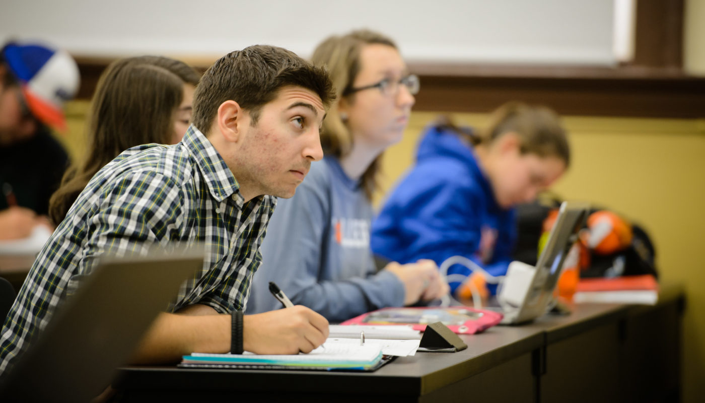 Student wearing plaid taking notes in a class in Holtzendorff