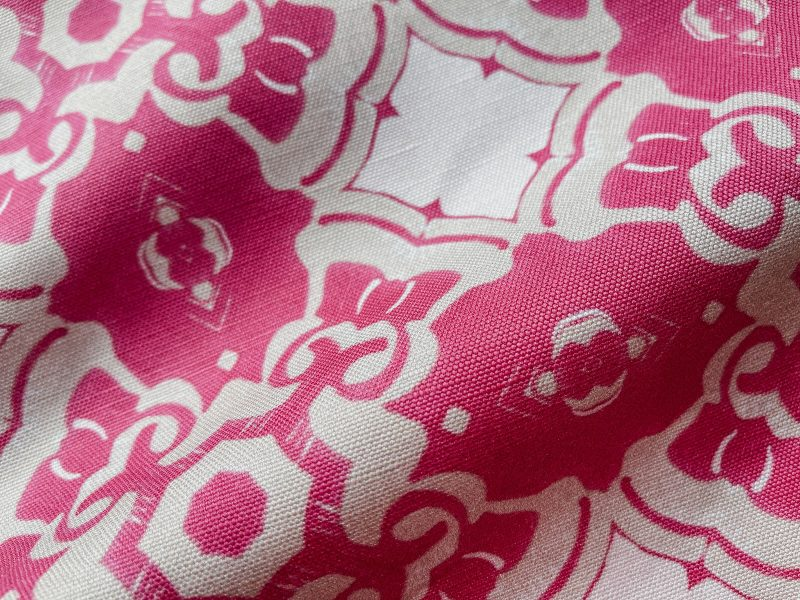 A fabric swatch of Pearl & Maude's medallion pattern Alexandria in berry magenta, cream and white