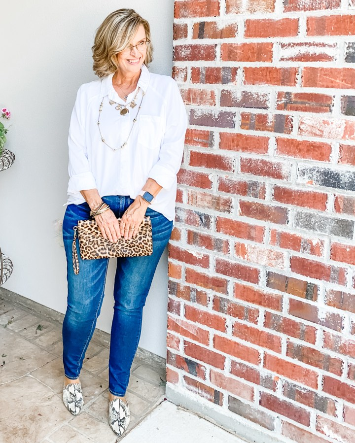 White buttondown top styled with jeans and animal print