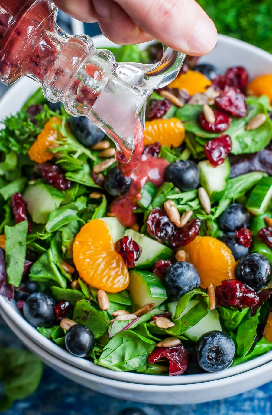 Pouring Balsamic Blueberry Salad Dressing on Salad