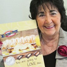 Carol Phillips of our Friendship Committee holds a small poster for Butter Braids.