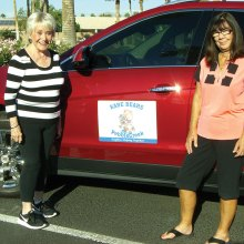 Joey Arnold (left), a driver for Kare Bears, is standing next to her car which has a Kare Bears removable magnet with Linda Glazer, Transportation Specialist.