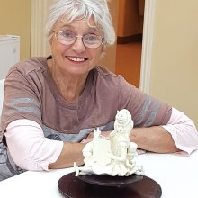 Sheila Millendorf with her sculpture Wonderland Story Teller.