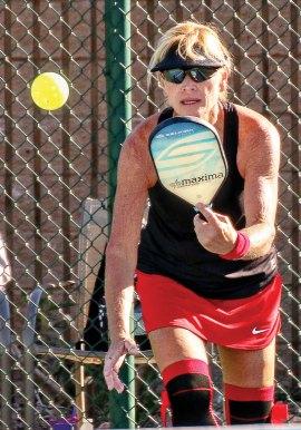 Robin Weaver returns a deep serve; Photo by Dannie Cortez.