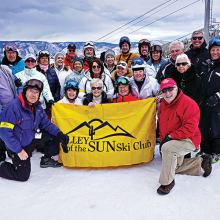 PC skiers Lynn Warren, Lew and Rose Geller together with other members of Valley of the Sun Ski Club pausing for a group photo with the Village Lift at Snowmass (Aspen) in the background; photo by Mary Ann Vangelisti.