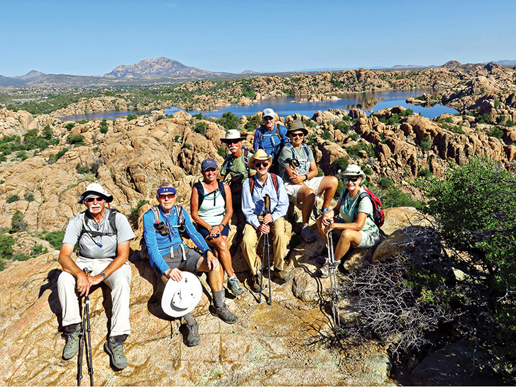 """Left to right: Wayne McKinney, Lynn Warren (photographer), Marilyn Reynolds, Dave Ausman (""""Ausy""""), Pete Williams (hike leader), Ed Bobigian, Diana Bedwell and Mary Hill relaxing in the Granite Dells high above Watson Lake with Granite Mountain in the background."""