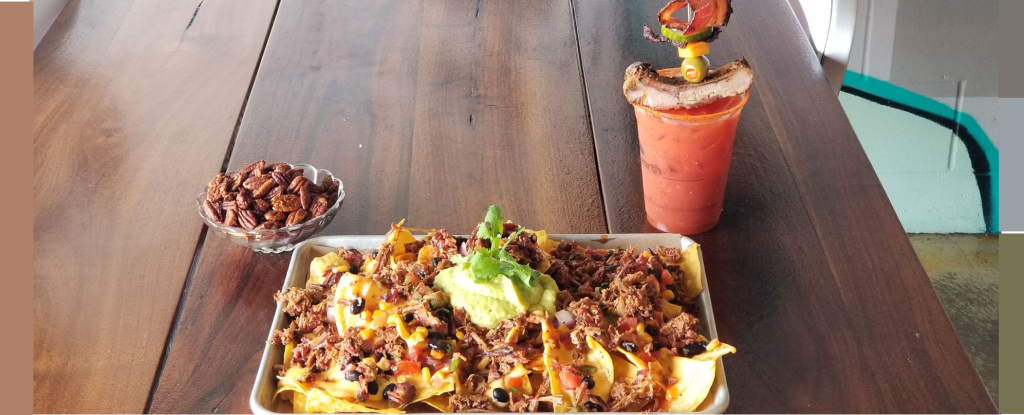 Mount Nacho - featuring homemade tortilla chips, queso, corn salsa, pickled guacamole, jalapeño and Pulled Pork - sits on a silver tray near a bowl of pecans and a Bloody Mary.