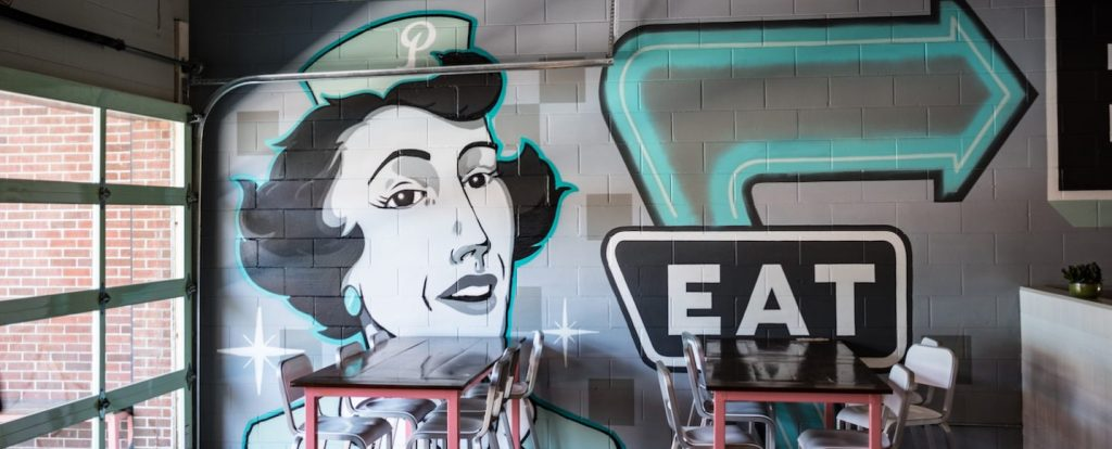 """A mural of a woman in mid-century garb with a """"P"""" hat and teal earrings adorns the East wall of Pecan Penny's restaurant"""