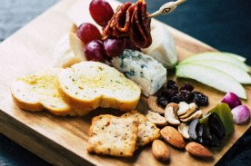 Cheese board with meats, nuts and apple slices