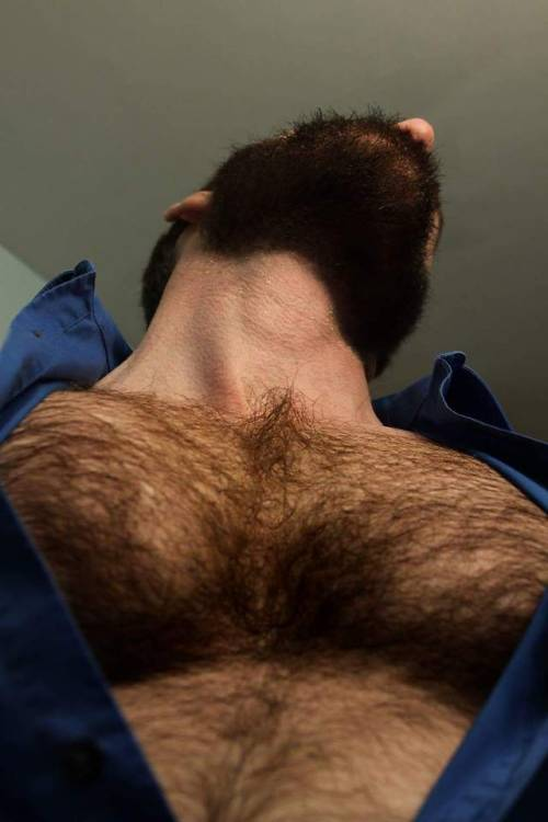 Man with head titled back showing his thick hairy chest in a partly-unbuttoned top.