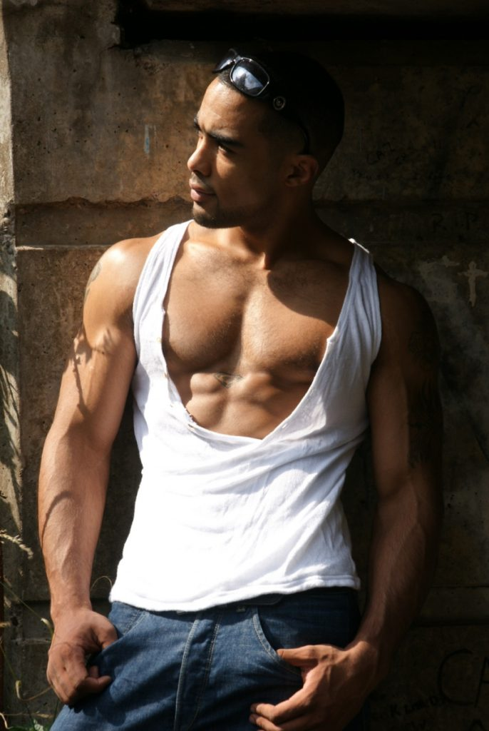 Quinton Hillocks posing in ripped tank top exposing chest and upper abs