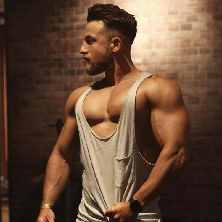 Viktor Dryndak pulling at tank top to show pec cleavage