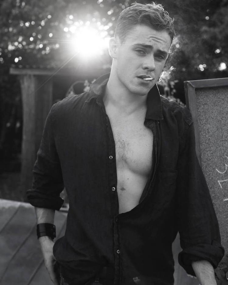 Dacre Montgomery cleavage in open shirt with cigarette facing camera