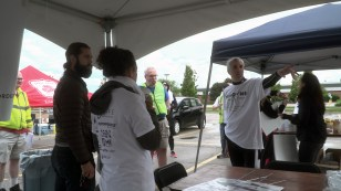 Ira David talks with event volunteers before the opening ceremony.