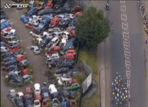 TdF cyclists race past crashed cars (screengrab from TdF coverage)