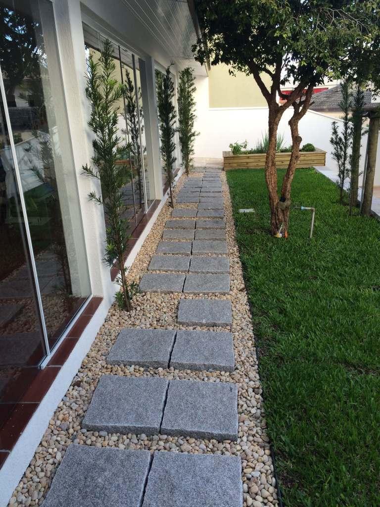 Jardim com pedra granito e gramas em volta