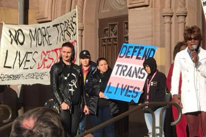 """A group of people holding signs celebrating Trans Day of Visibility. One sign says """"Defend Trans Lives"""" on blue and pink. A banner says """"No more trans lives destroyed"""""""
