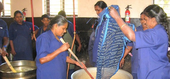 9.1 two women taking a cloth out of dye pot - Copy