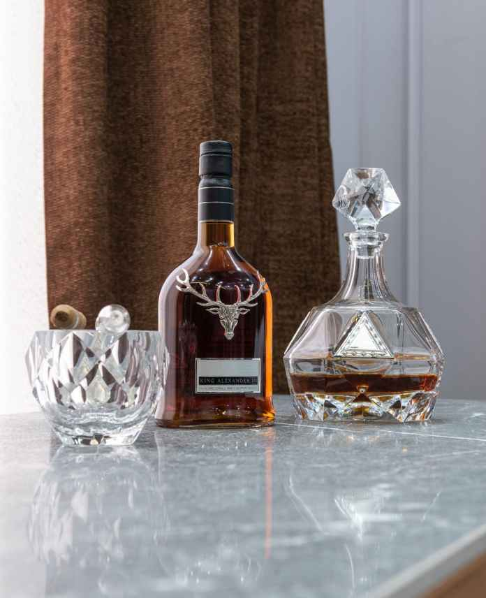 bottle of whiskey between decanter and ornamental glass with cigar