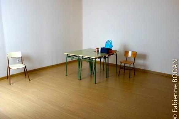 A l'étage une grande pièce, avec des petites tables et chaises d'écoliers. © Fabienne Bodan