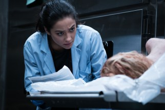 Megan (Shay Mitchell) tries to compare the picture of Hannah's driver's license with her brutalized corpse in Screen Gems' THE POSSESSION OF HANNAH GRACE.