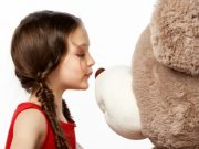 Portrait of a little brunette girl kissing a teddy bear into it's nose isolated on white background, close up