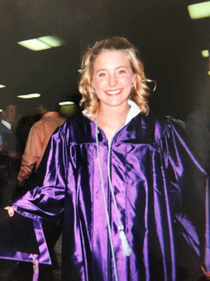 young high school graduate wearing a purple graduation gown