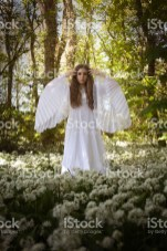 Beautiful woman in long white medieval dress standing in a forest on a carpet of flowers looking straight to camera
