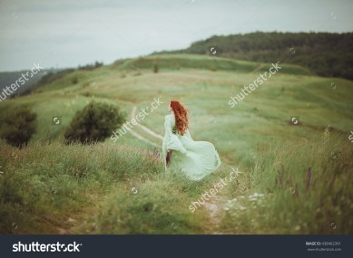 stock-photo-young-redhead-girl-in-medieval-dress-walking-through-field-with-sage-flowers-freedom-concept-438462391
