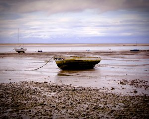 an old barnacled boat lying on the mud after the tide has gone out
