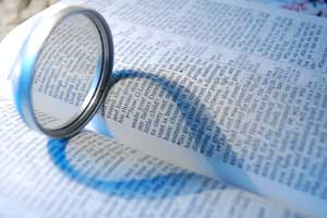 Bible with a magnifying glass on it, making a heart-shaped shadow