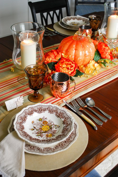 Autumn tablescape with budget friendly pumpkin centerpiece, Mason's ironstone, striped table runner, glass hurricanes, fall florals, and copper mugs.
