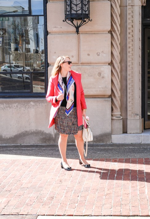 Blond woman in pink coat and tweed skirt with colorful scarf on street.