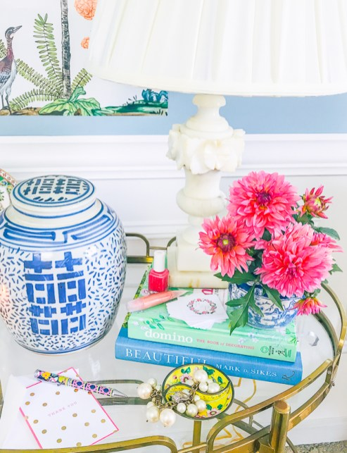 pink dahlias in mini blue and white ginger jar on book stack