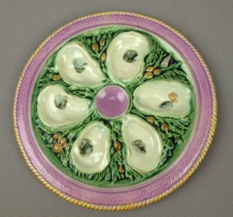 Majolica oyster plate with pink rim and wells shaped like oysters.