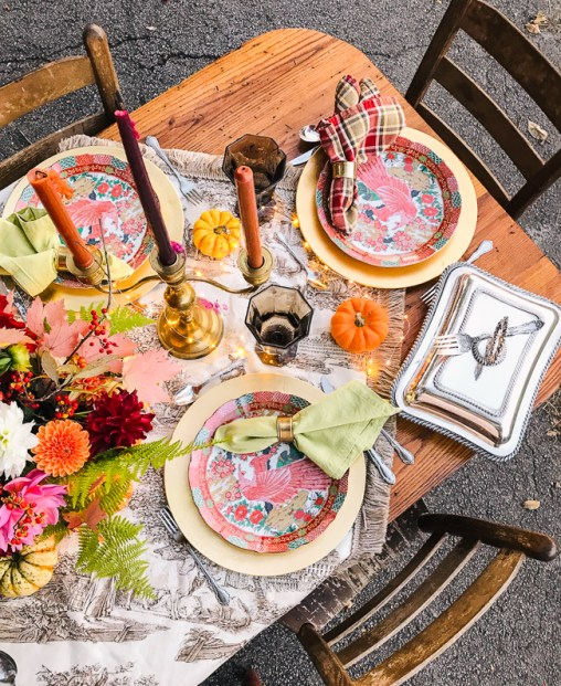 Overtop view of this rustic Chinoiserie Thanksgiving tablescape set with Peacock plates in orange and green, gold chargers, brass candelabras, and toile and plaid linens.