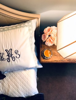 Bed with monogramed pillow and nightstand with lamp, peonies, and cup of tea