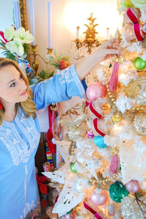 Katherine hangs ornament on tree in blue vintage caftan