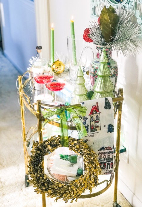Gold bar cart styled for holidays with candles, glass Christmas trees, Rose Medallion, and wreath