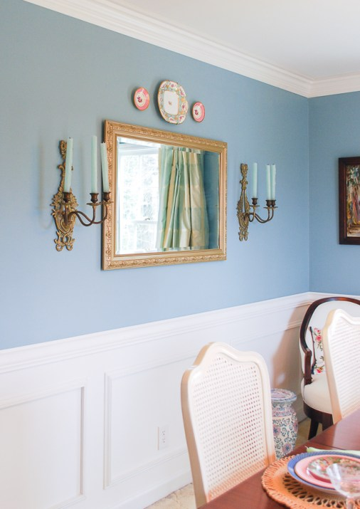 aqua dining room wall with mirror, bronze sconces, wainscoting and crown molding
