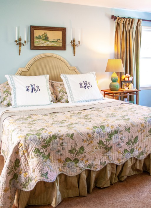 Made bed in grandmillennial bedding including pink chintz quilt, monogrammed pillows, and percale sheets.