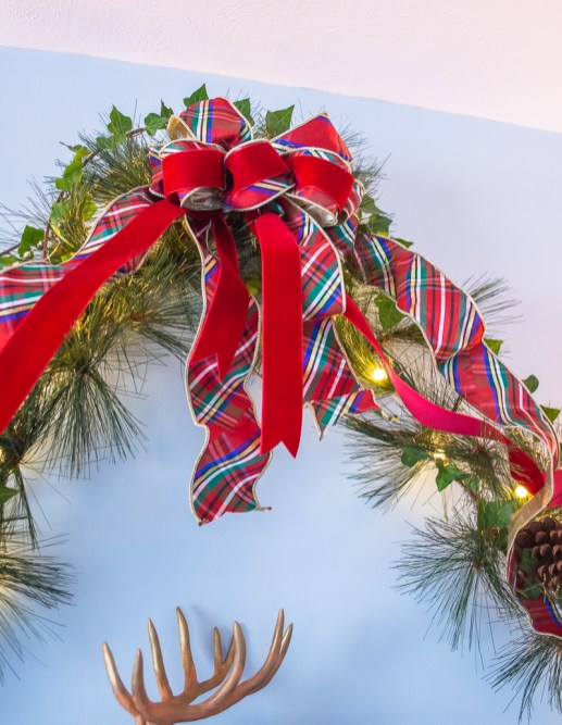 Plaid and red velvet multi-loop bow decorates the peak of the pine and ivy garland swags