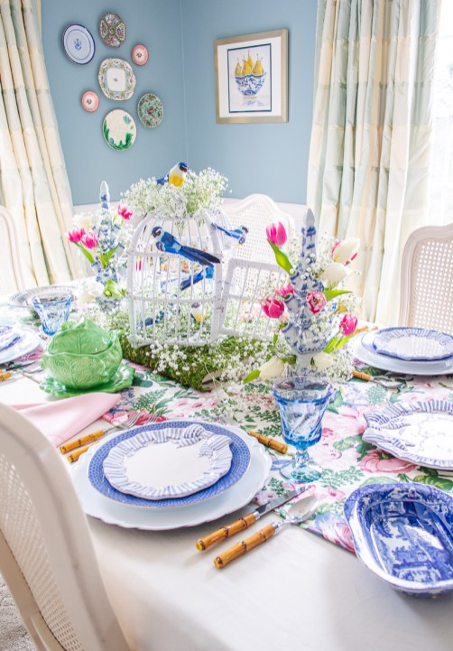 White wicker bird cage decorated with blue songbirds and baby's breath creates a whimsical spring centerpiece on this tablescape