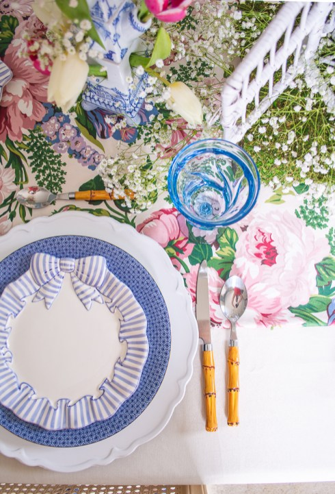 A pacesetting with Haldon Group bow salad plates, Mottahedeh blue lace dinner plates, white chargers, bamboo flatware, and blue glasses