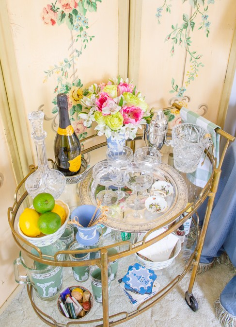 Top view of vintage bar cart decor including silver tray, coupes, fresh flowers, crystal ice bucket, and champagne