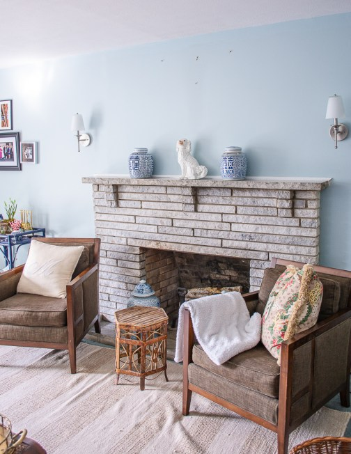Family room refresh before photo of mantel and brown arm chairs